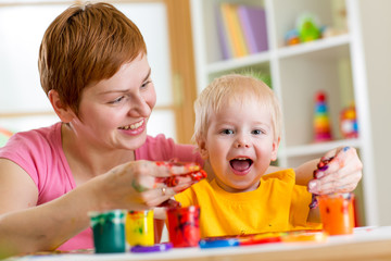 mother and toddler boy paint together at home