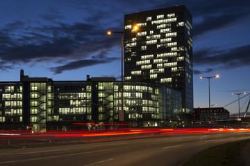 Befahrene Straße in München mit Bürogebäude bei Nacht