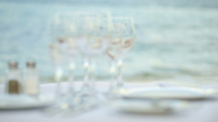Served table with empty dishware against sea background