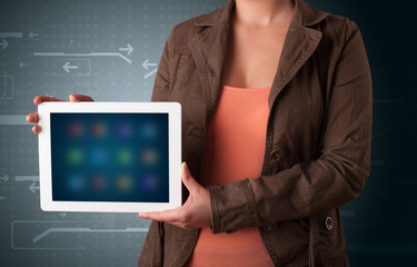 Woman holding a white tablet with blurry apps