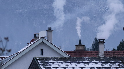 Fossil fuel heating concept Residential chimneys and white smoke