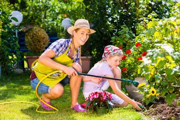 Mutter und Tochter wässern Blumen im Garten