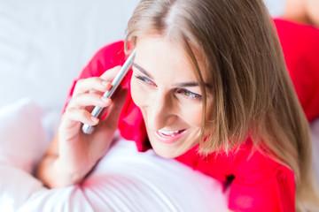 Frau telefoniert mit Smartphone auf Bett