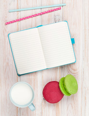 Cup of milk and macarons on white wooden table with notepad