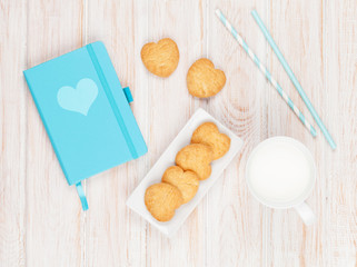Cup of milk, heart shaped cookies and notepad