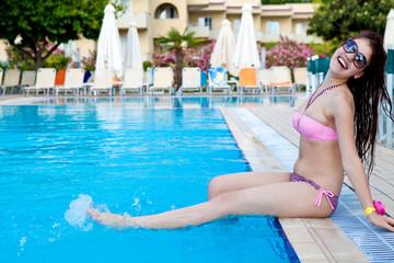 Девушка сидит у бассейна с водой