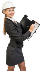 Businesswoman wearing hard hat, writing on clipboard