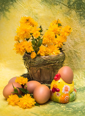 Eggs and spring flowers with a figure of a chicken