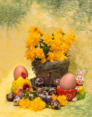 Eggs and spring flowers with a figure of chicken