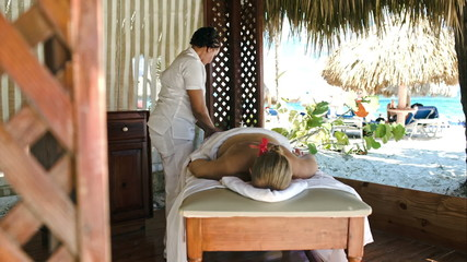 Woman getting professional massage on tropical resort