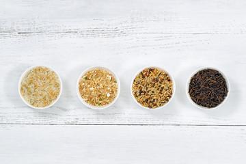 Varieties of Rice in bowls on top of White Wood