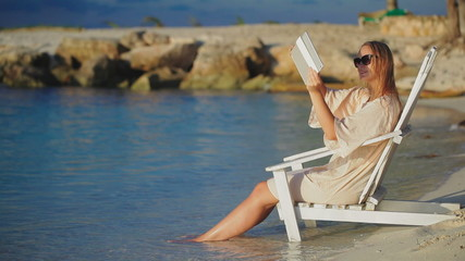 Woman with pad making photos of sea sitting in deck chair on