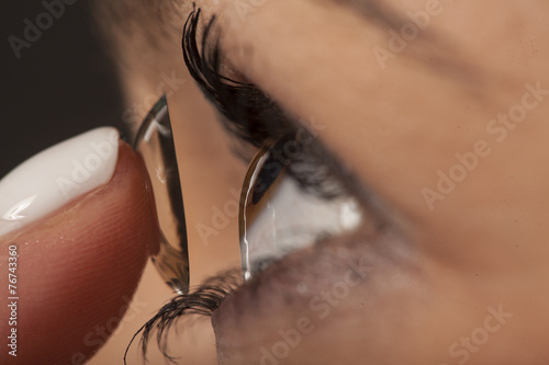 A woman putting on contact lenses