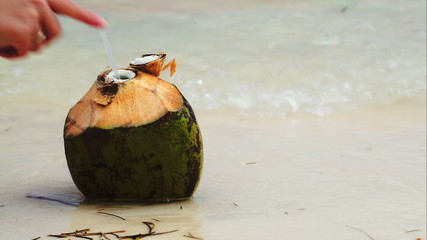 Coconut by the sea with female hand putting a straw there