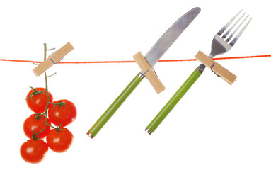 Fork, knife and ripe red tomatoes hanging from clothesline