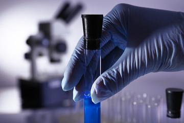 Laboratory glassware with blue liquid in hand of scientist