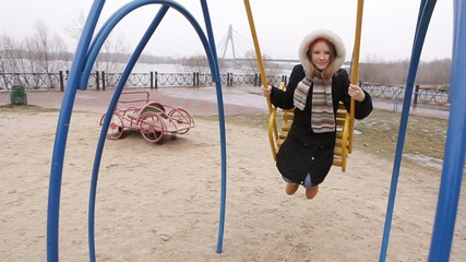 Girl enjoying a swing ride on a playground in a park on a nice