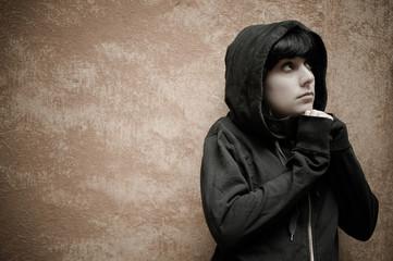 Dark young woman sad standing near urban wall portrait
