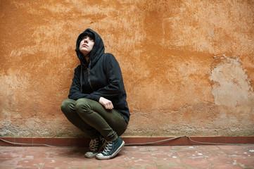 Dark young woman sad crouched near urban wall portrait