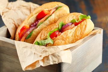 Sandwiches with salmon in wooden box on dark wooden background