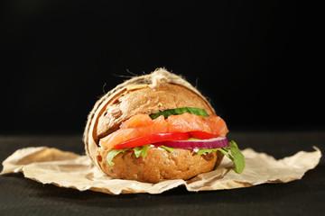 Sandwich with salmon on dark background