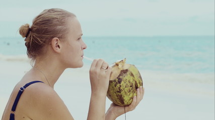 Woman on the beach drinking from coconut