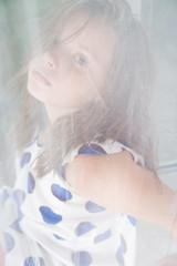 Портрет маленькой девочки за сетчатой тюль