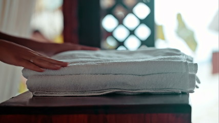 Woman putting fresh towels on the table and flower on it