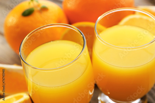 Glass of orange juice and slices on wooden table background - 76745948