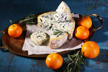 Blue cheese with sprigs of rosemary and oranges