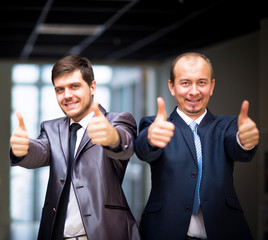 business people with thumbs up and smiling