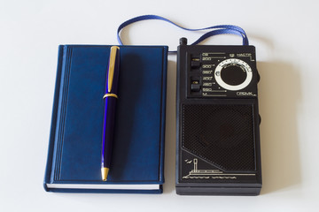Retro radio receiver, notepad and pen.