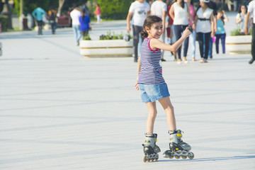 The  girl  rides on roller skates in the park
