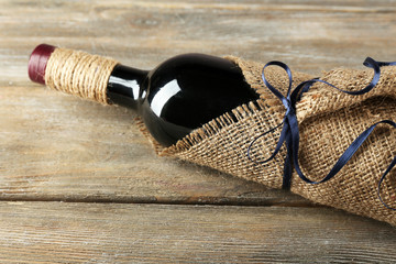 Red wine bottle wrapped in burlap cloth