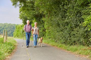 Senioren gehen Gassi mit Hund im Herbst