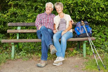 Paar beim Wandern macht Pause auf Bank