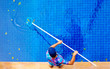 Leinwanddruck Bild - young adult man, personnel cleaning the pool from leaves