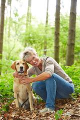 Lächelnde Seniorin mit Hund im Wald