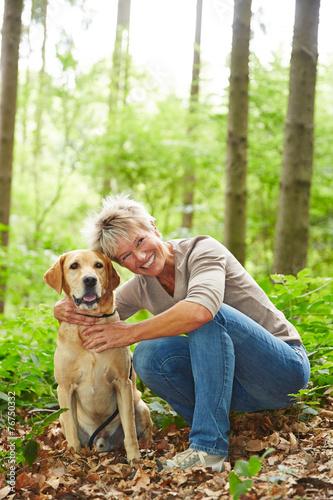 canvas print picture Lächelnde Seniorin mit Hund im Wald