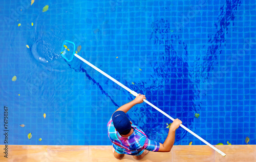 Leinwanddruck Bild young adult man, personnel cleaning the pool from leaves