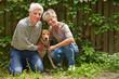 Mann und Frau mit Hund im Garten