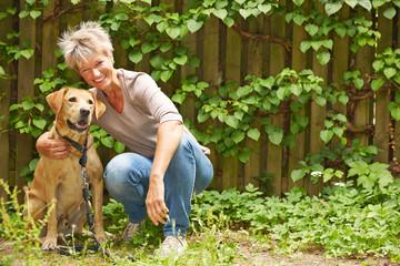 Ältere Frau mit Hund im Garten