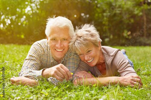 canvas print picture Paar Senioren liegt auf Wiese