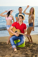 Friends Enjoying at the Beach with Guitar.