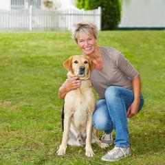 Ältere Frau mit Labrador Retriever im Garten