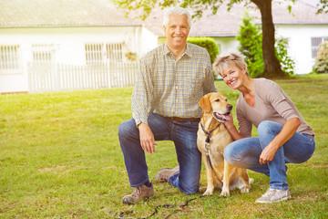 Paar Senioren vor Haus mit Labrador Retriever