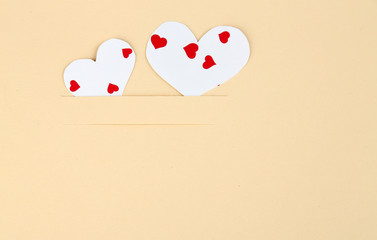 Paper hearts on beige background, close up