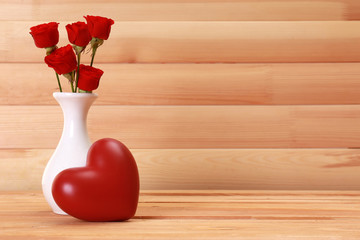 Love concept. Roses and heart on wooden background