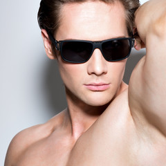 Portrait of young muscular sexy man in glasses.