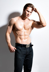 Muscular handsome man with hands behind head.